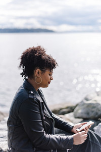 black woman sitting on rocks in front of water looking at phone
