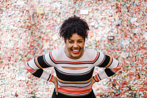 black woman smiling with hands on hips in front of colorful wall