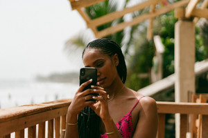 Black woman snapping a photo on her cell phone