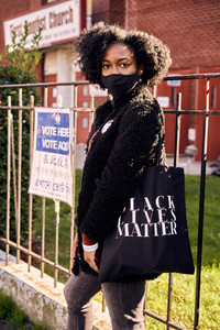 Black woman standing in line to vote with Black Lives Matter bag
