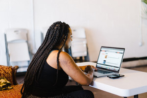 black woman staring at laptop on small desk