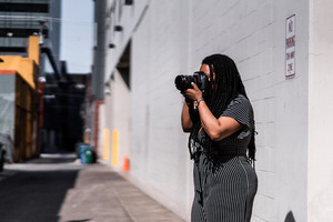 black woman wearing black and white jumpsuit taking a photo between buildings