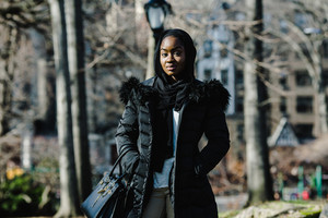 black woman wearing black coat standing in front of trees and lightpost