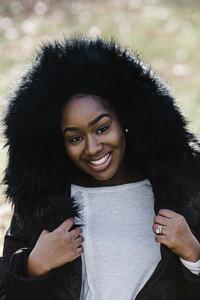 black woman wearing black fur hood and white tshirt outside