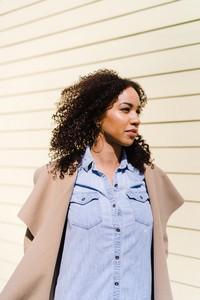 black woman wearing coat walking outside