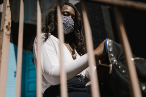 Black woman wearing face mask and holding backpack
