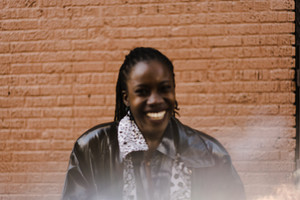 black woman wearing leather jacket in front of brick wall smiling