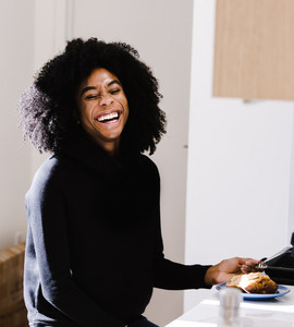 black woman with huge smile in kitchen