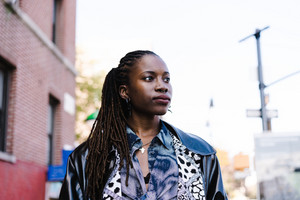 black woman with leather jacket and piercings standing outside