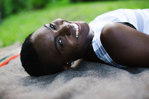 black woman with short hair lying on floor looking at camera smiling