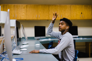 black young adult raising hand in computer lab