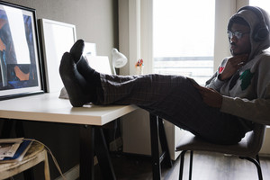 black young adult wearing hood listening to headphones with feet up on desk