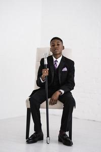 boy holding a fancy cane in a Black suit