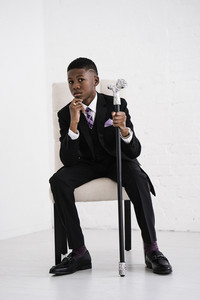 boy holding a fancy cane in a Black suit