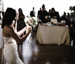 Bride throwing a bouquet into a crowd