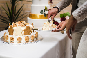 brown and black hands holding slice of wedding cake