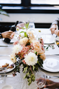 centerpiece filled with pink flowers on a dining table