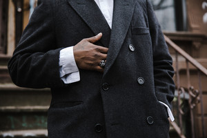 Close up of Black man in a black coat holding the top of his stomach