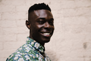 closeup of black man wearing floral shirt and smiling