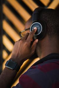 closeup of black man wearing glasses, watch, and headphones