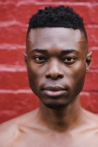 closeup of black man's face in front of red wall