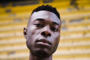 closeup of black man's face in front of yellow wall