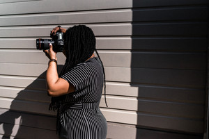 closeup of woman wearing black and white taking a picture in front of a grey wall