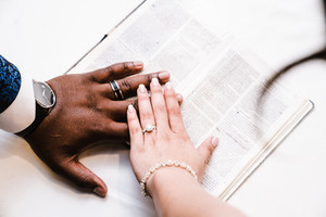 Couple placing hands over Bible with wedding rings
