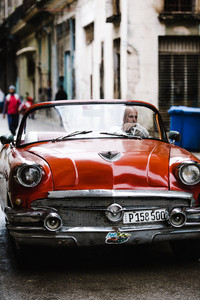 cuban man driivng red vintage convertible