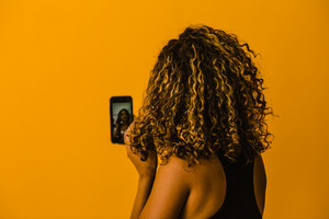 curly hair latina woman looks at her phone