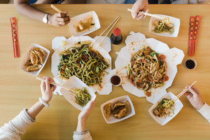 diverse group of friends sharing food with chopsticks