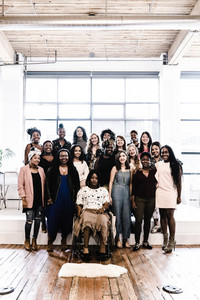 diverse group of women standing behind black woman in wheelchair