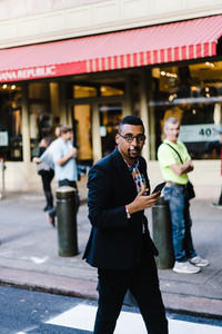 East African man walking with cell phone