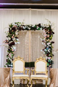 elegant decor with flowers surround two fancy white wedding chair
