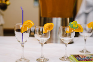 empty glass flutes with straws and orange slices