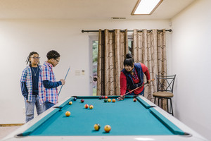 family of three play pool together