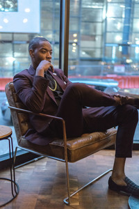 fashionable man in a suit and plaid loafers sits at a cafe