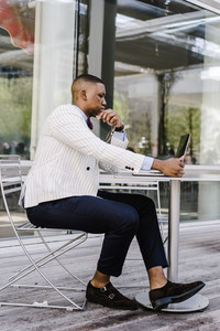fashionable man in a suit sits outside on the phone