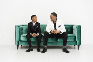 Father and son looking at each other on green couch