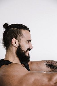 fit gentleman with a man bun shows his muscles