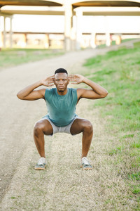 fit man does exercises on an outside track