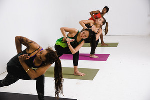 four women in yoga outfits stretch out on different colored maps