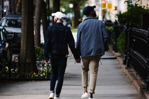 gay interracial couple walking down street holding hands
