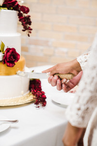 groom cutting into fancy wedding cake