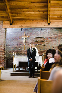 Groom in a tux standing at the aisle on his wedding day