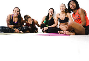 Group of diverse women laughing while sitting on their yoga mats