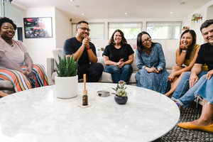 Group of innovative and diverse creators sit around a couch and talk