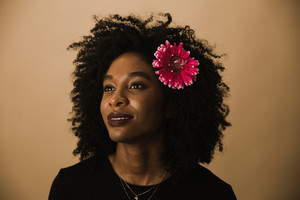 Guyanese woman posing with flower in her curly hair