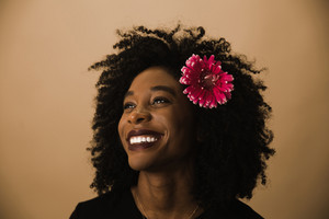 Guyanese woman smiling with flower in curly hair