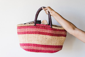 Hand woven basket outfitted with a leather wrapped handle
